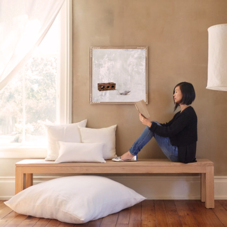 interior design woman with book and painting of brick and feather
